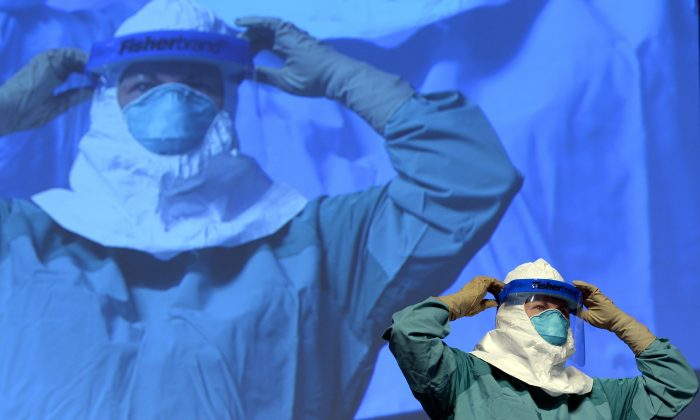 Barbara Smith, a nurse at Mount Sinai Health Systems and a CDC official demonstrate the proper technique for donning protective gear during an Ebola educational session for healthcare workers at the Jacob Javits Center in New York, Oct. 21, 2014. (Timothy A. Clary/AFP/Getty Images)