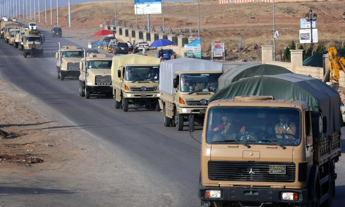 Dozens of Kurdish peshmerga fighters drive through Arbil after leaving a base in northern Iraq on Oct. 28, 2014, on their way to the battleground Syrian town of Kobani. 'Forty vehicles carrying machineguns and weapons and artillery with 80 of the peshmerga forces will head to Dohuk (province) and then cross the border today,' a Kurdish officer told AFP. A further 72 will fly to Turkey the following day, the officer said. The town on the Turkish border has become a crucial front in the fight against the Islamic State (IS) group, which overran large parts of Iraq in June and also holds significant territory in Syria. (Safin Hamed/AFP/Getty Images)