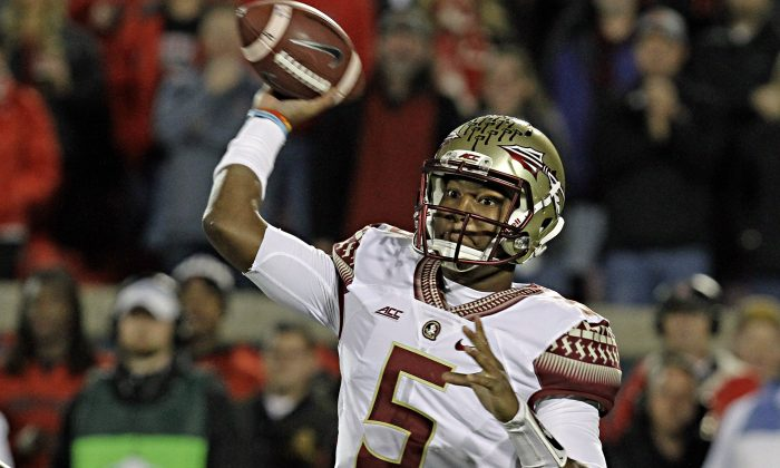 Florida State quarterback Jameis Winston (5) looks to pass in the first half of a NCAA college football game against Louisville in Louisville, Ky., Thursday, Oct. 30, 2014. (AP Photo/Garry Jones)