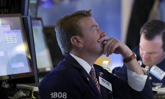 Specialist Michael O'Mara (L) works on the floor of the New York Stock Exchange Wednesday, Oct. 15, 2014. (AP Photo/Richard Drew)