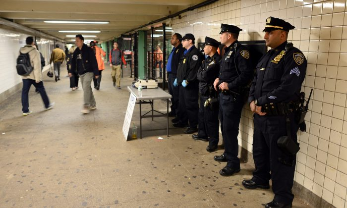 New York Police Department (NYPD) officers man a checkpoint at the entrance of a subway station in Queens, New York, on Oct. 24, 2014, one day after a man charged at four New York police officers with a metal hatchet, hitting two of them. (Jewel Samad/AFP/Getty Images)