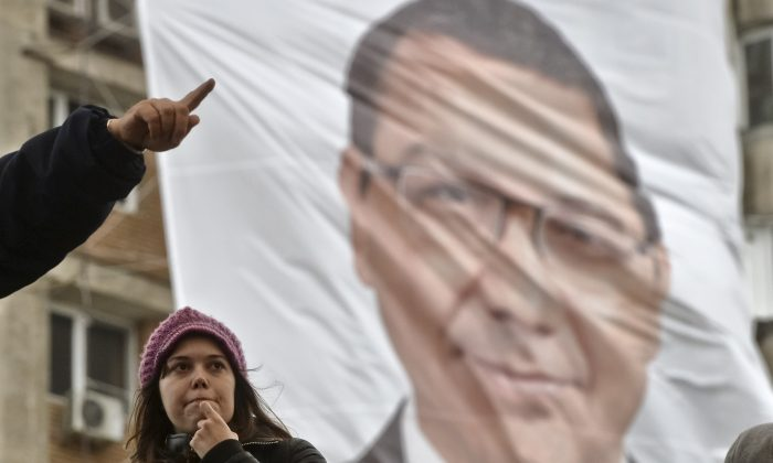 A man gives directions to a young woman, in Bucharest, Romania, Saturday, Oct. 25, 2014, backdropped by a campaign poster, attached to the facade of an apartment block, depicting Prime Minister Victor Ponta, leader of the ruling Social Democracy Party (PSD) who runs for president in elections set to take place on Nov. 2.  Several prominent members of the PSD came under investigation for corruption related crimes in recent weeks, ahead of the presidential election in which the Social Democratic Party leader, Prime Minister Victor Ponta, is the favorite. Ponta says the probes will not harm his chances. (AP Photo/Andreea Alexandru, Mediafax) ROMANIA OUT