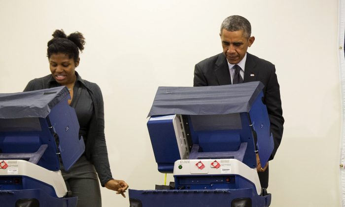 FILE - In this photo taken Oct. 20, 2014, President Barack Obama votes next to Aia Cooper at the Dr. Martin Luther King Community Service Center in Chicago. (AP Photo/Evan Vucci,File)