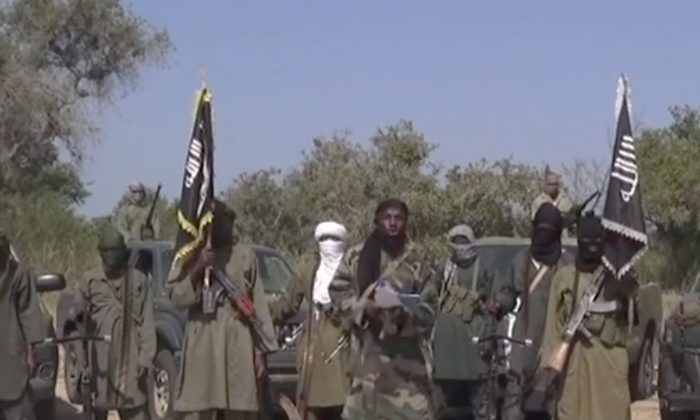 This Friday Oct. 31, 2014 image taken from video by Nigeria's Boko Haram terrorist network, the leader of Nigeria's Islamic extremist group Boko Haram, center, has denied agreeing to any cease-fire with the government and said Friday more than 200 kidnapped schoolgirls all have converted to Islam and been married off. (AP Photo)
