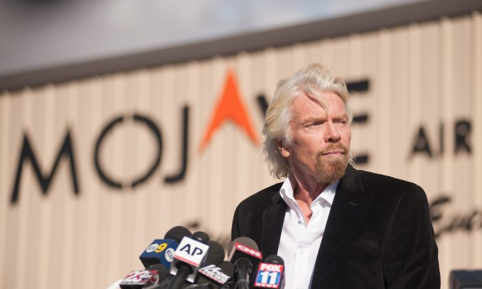 Virgin founder Sir Richard Branson speaks at a press conference at the Mojave Air and Space Port in Mojave, California on Nov. 1, 2014. British tycoon Richard Branson insisted Saturday his dream of commercial space travel remained alive but warned his company would not 'press on blindly' without knowing what caused the spacecraft crash that killed one pilot and seriously injured another. Speaking to reporters after arriving in the California facility which had been the hub of Virgin Galactic's ambitious space program, Branson said safety remained his paramount concern. 'We owe it to our test pilots to find out exactly what went wrong, and once we've found out what went wrong, if we can overcome it, we'll make absolutely certain that the dream lives on,' Branson told reporters. His comments at the Mojave Air and Space Port came as a team of federal investigators began probing the causes of Friday's accident, which dealt a devastating setback to the cause of commercial space tourism. (Josh Edelson/AFP/Getty Images)