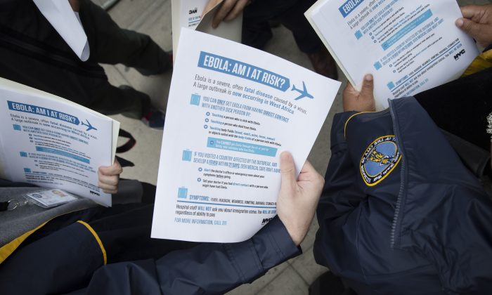 Members of the Brooklyn Borough President's office hand out fliers detailing the risks of Ebola outside The Gutter bowling alley in Brooklyn's Williamsburg neighborhood, in New York, on Oct. 24, 2014. Top medical experts studying the spread of Ebola say the public should expect more cases to emerge in the United States by year's end as infected people arrive here from West Africa, including American doctors and nurses returning from the hot zone and people fleeing from the deadly disease. No one knows for sure how many infections will emerge in the US or anywhere else, but scientists have made educated guesses based on data models that weigh hundreds of variables, including daily new infections in West Africa, airline traffic worldwide and transmission possibilities. (AP Photo/John Minchillo)