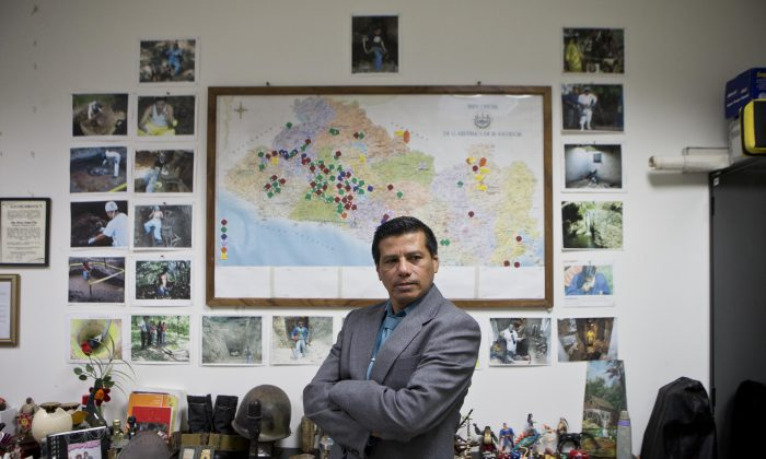 """Criminologist Israel Ticas poses for backdropped by a wall papered with images of his team members at work and a map of El Salvador marking points of reported violent cases, in San Salvador, on Aug 20, 2014. Ticas calls himself the """"lawyer for the dead,""""  who sees the evidence of gang rape and sadistic methods of murder on a daily basis. (AP Photo/Esteban Felix)"""