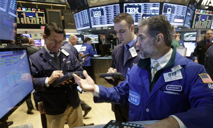 Specialist Anthony Rinaldi (R) works at his post on the floor of the New York Stock Exchange, Friday, Oct. 31, 2014. (AP Photo/Richard Drew)
