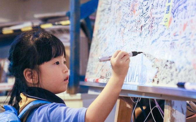 "A little girl draws on a whiteboard that is filled with messages of hope and peace at what protesters are calling ""Umbrella Square,"" in the Central District of Hong Kong, on Nov. 1, 2014. (Benjamin Chasteen/Epoch Times)"