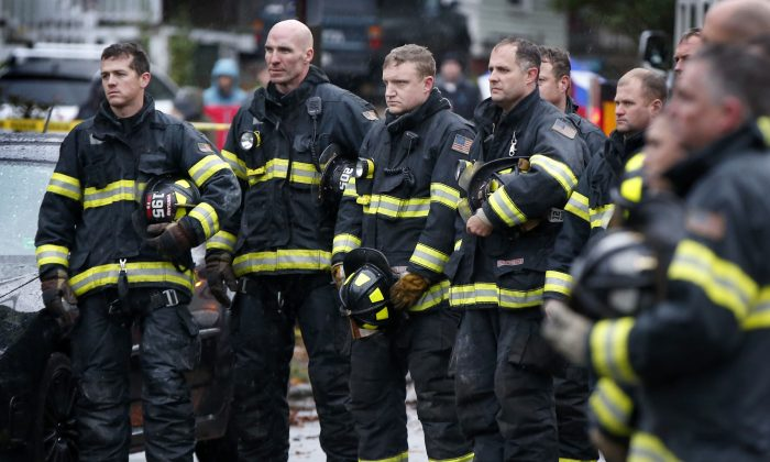Firefighters take their helmets off as a body is removed from the scene of a fatal apartment building fire in Portland, Maine on Saturday, Nov. 1, 2014. Earlier in the morning, a fatal fire swept through a two-apartment building housing students from the University of Southern Maine. (AP Photo/Robert F. Bukaty)