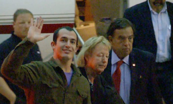 This image taken from a video shows Marine Sgt. Andrew Tahmooressi waving after arriving in Miami on Saturday, Nov. 1, 2014 in Weston, Fla. Tahmooressi is back home after a Mexican judge ordered his release from jail, where he spent eight months for crossing the border with loaded guns. Family spokesman Jon Franks told reporters that Tahmooressi arrived at a South Florida airport about 6 a.m. Saturday. Franks said Tahmooressi was resting with his family at their home suburban Weston, Fla. (AP Photo/Raul Torres)