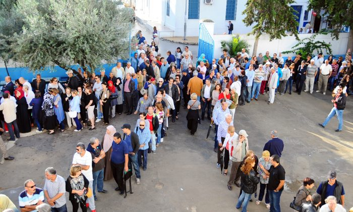 Tunisians queue outside a polling station in La Marsa, Tunisia, Sunday, Oct. 26, 2014. Tunisians expressed tentative hope for the future as they lined up early Sunday to choose their first five-year parliament since they overthrew their dictator in the 2011 revolution that kicked off the Arab Spring. (AP Photo/Hassene Dridi)