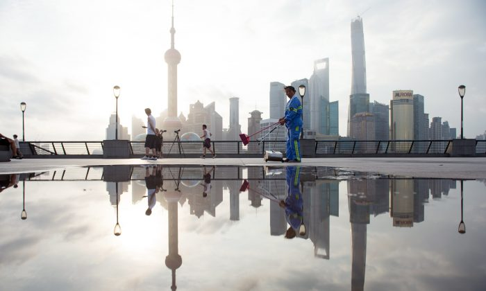 A worker cleans the promenade on the Bund along the Huangpu River against the skyline of the Lujiazui Financial District in Pudong in Shanghai on July 24, 2014. (Johannes Eisele/AFP/Getty Images)