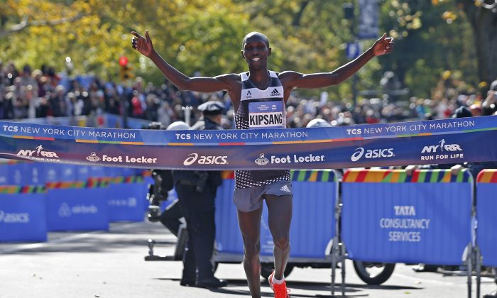 Wilson Kipsang of Kenya celebrates as he hits the tape to win the men's division of the the 44th annual New York City Marathon in New York, Sunday, Nov. 2, 2014. Kipsang won in an unofficial time of 2 hours, 10 minutes, 59 seconds. (AP Photo/Kathy Willens)