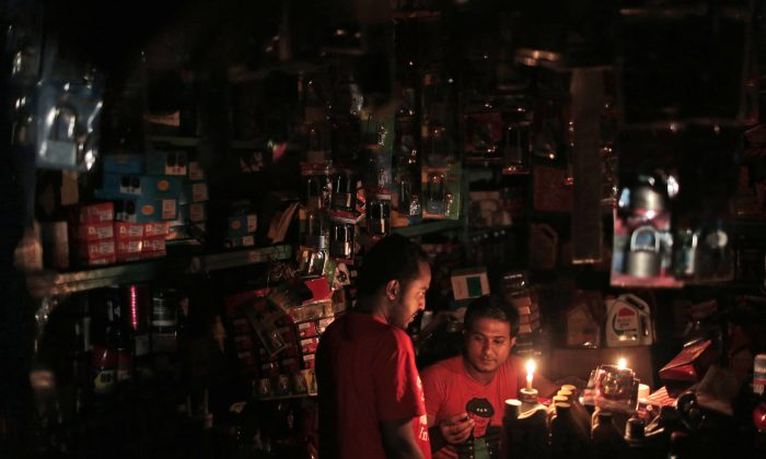 A Bangladeshi salesman interacts with a customer during a blackout in Dhaka, Bangladesh, Saturday, Nov. 1, 2014. Bangladesh was struggling to restore power late Saturday, hours after being hit with a nationwide blackout that started when a transmission line bringing electricity from neighboring India failed, officials said. The system was not expected to be fixed until at least early Sunday. (AP Photo/A.M. Ahad)