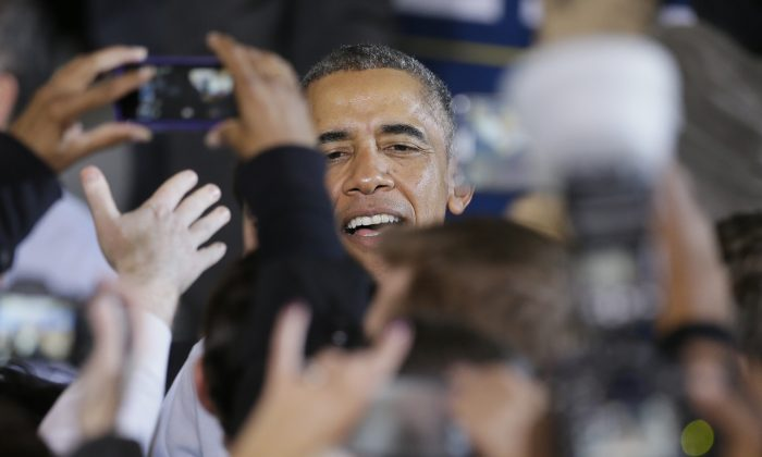 President Barack Obama greets supporters at Wayne State University in Detroit, Saturday, Nov. 1, 2014. Obama's attendance is in support of democrats, gubernatorial candidate Mark Schauer and U.S. Senate candidate Gary Peters. (AP Photo/Carlos Osorio)
