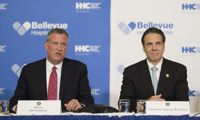 New York City Mayor Bill de Blasio (L) joins New York Gov. Andrew Cuomo at a news conference at Bellevue Hospital in New York, Oct. 23, 2014, after New York City physician Dr. Craig Spencer had tested positive for the Ebola virus. De Blasio has received high marks from pundits, who praise his reassuring, consistent tone when discussing the disease, a sharp contrast to the haphazard, and at times borderline hysterical, tone from Cuomo and New Jersey Governor Chris Christie. (AP Photo/John Minchillo)