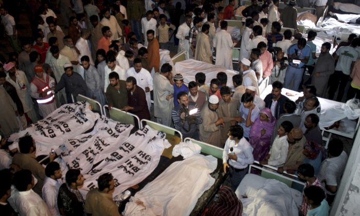 Pakistanis gather to identify bodies of their relatives killed in a bomb blast at a local hospital in Lahore, Pakistan, Nov. 2, 2014. A bomb exploded near a Pakistani paramilitary checkpoint Sunday, killing scores of people near the country's eastern border with India in an attack suspected to be the work of a suicide bomber, police said. (AP Photo/K.M. Chaudary)