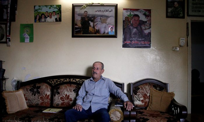 Ramadan Haidar, father of Mahmoud, a 23-year-old Syrian who was killed while fighting in the military, sits in his living room under photos of his son, in the city of Tartous, the capital of a coastal province in Syria on Oct. 28, 2014. (AP Photo/Diaa Hadid)