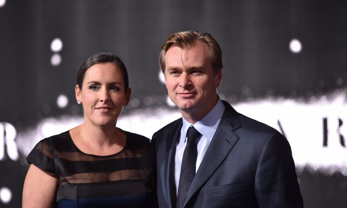British-US director Christopher Nolan (R) poses with his wife British producer Emma Thomas (L) on the red carpet for the European premiere of the film 'Interstellar' in London on October 29, 2014. AFP PHOTO / LEON NEAL (Photo credit should read LEON NEAL/AFP/Getty Images)