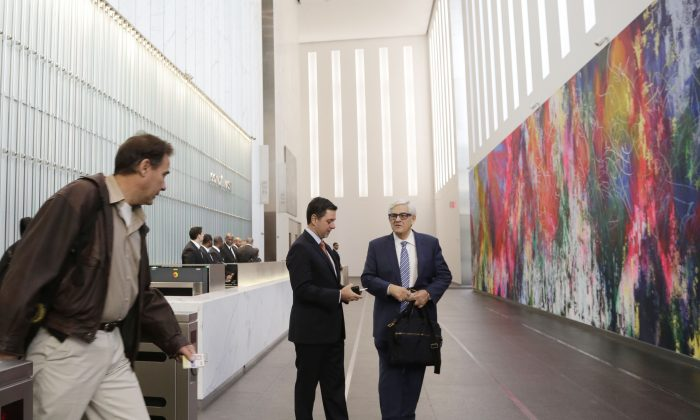 An employee enters the lobby of One World Trade Center in New York on Monday, Nov. 3, 2014. Thirteen years after the 9/11 terrorist attack, the resurrected World Trade Center is again opening for business, marking an emotional milestone for both New Yorkers and the United States as a whole. (AP Photo/Mark Lennihan)