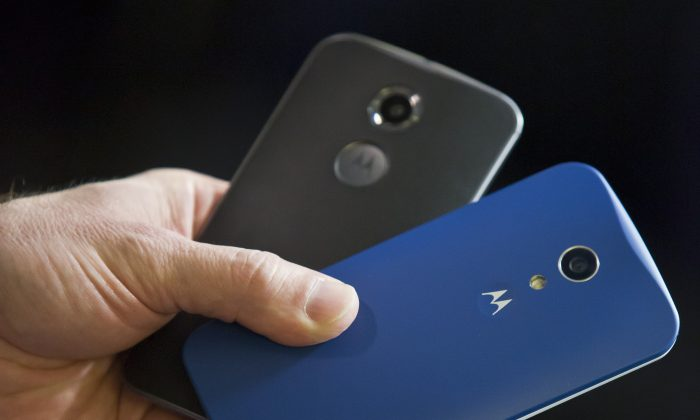 Steve Sinclair, Motorola's vice president of product management, shows the new Moto X, left, and Moto G phones during an interview, Wednesday Aug. 27, 2014 in New York.  (AP Photo/Bebeto Matthews)