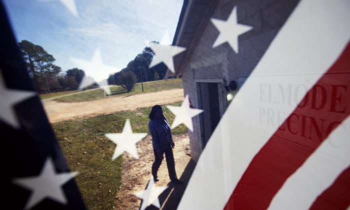 Woman is seen through an American flag as she walks into the Elmodel precinct to cast her ballot, Tuesday, Nov. 4, 2014, in Elmodel, Ga. (AP Photo/David Goldman)