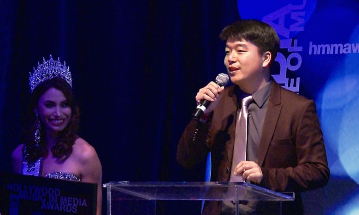 Tony Chen accepts the Hollywood Music in Media Award for best song in the World Music category in Hollywood, Calif. on Nov. 4. (Eric Zhang/Epoch Times)
