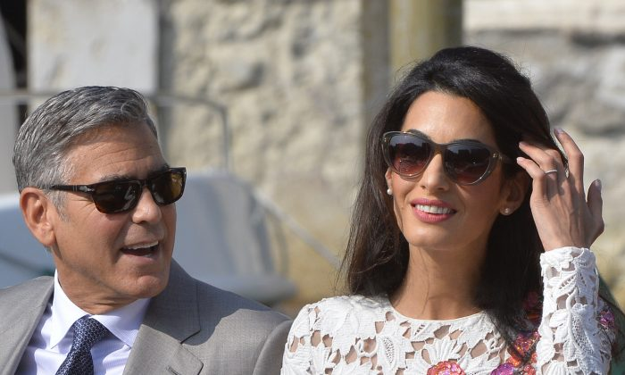 US actor George Clooney and his wife Amal Alamuddin stand on a taxi boat on the Grand Canal on September 28, 2014 in Venice. (AFP/Getty Images)
