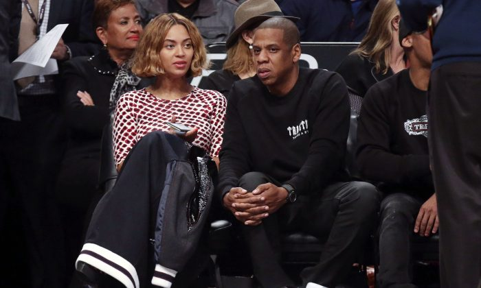 Entertainers Beyonce and Jay Z attend an NBA basketball game between the Brooklyn Nets and the Oklahoma City Thunder, Monday, Nov. 3, 2014, in New York. (AP Photo/John Minchillo)