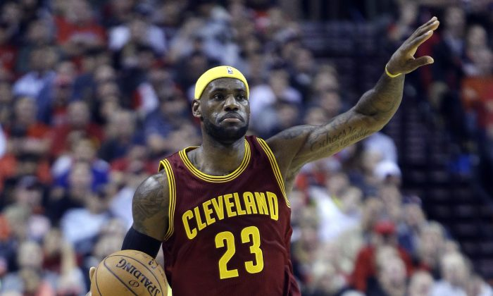Cleveland Cavaliers forward LeBron James calls out a play as he brings the ball down court during the first half of an NBA basketball game against the Portland Trail Blazers in Portland, Ore., Tuesday, Nov. 4, 2014.(AP Photo/Don Ryan)