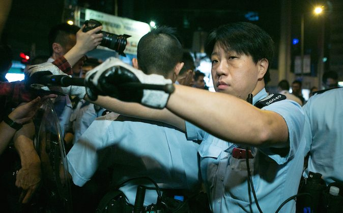 A police officer is holding back and blocking the media as a protester is on the ground being arrest after a clash with the police in Monk Kok, Hong Kong, on Nov. 6, 2014. (Benjamin Chasteen/Epoch Times)