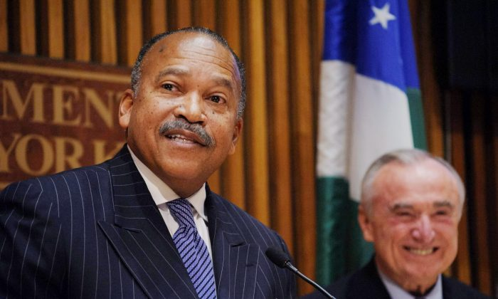 Benjamin Tucker, left, newly appointed first deputy commissioner for the New York Police Department, smiles from the stage after being introduced to the media by New York Police Commissioner William J. Bratton, right, during a news conference at NYPD headquarters in New York, Wednesday, Nov. 5, 2014. (AP Photo/Newsday, Charles Eckert)