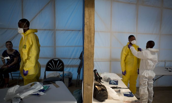 This undated handout photo issued by Save the Children UK on Wednesday, Nov. 5, 2014, shows prospective health care workers in the Kerry Town Ebola Treatment Centre being tested on their personal protection equipment procedure in Sierra Leone. (AP Photo, Louis Leeson/Save the Children UK)