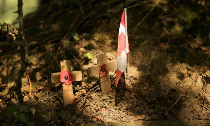 """Memorial crosses and a Canadian flag sit in the ground near the dressing station in Ypres, Belgium, where Lt.-Col. John McCrae treated the wounded and composed his famous poem """"In Flanders Fields"""" after burying his friend. On Nov. 6, 2014, a plaque will be unveiled in Guelph honouring McCrae, whose famous World War I poem became the inspiration behind the Remembrance Day poppy. (Christopher Furlong/Getty Images)"""