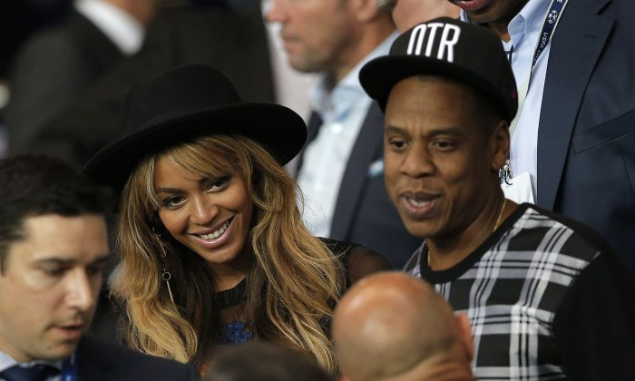 In a Tuesday, Sept. 30, 2014 file photo, Beyonce and her husband Jay Z stand up at half time in the Champions League soccer match between PSG and Barcelona, at the Parc des Princes stadium, in Paris. (AP Photo/Christophe Ena, File)