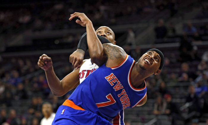 New York Knicks forward Carmelo Anthony (7) and Detroit Pistons forward Caron Butler (31) battle for a rebound in the second half of an NBA basketball game in Auburn Hills, Mich., Wednesday, Nov. 5, 2014.  (AP Photo/Paul Sancya)