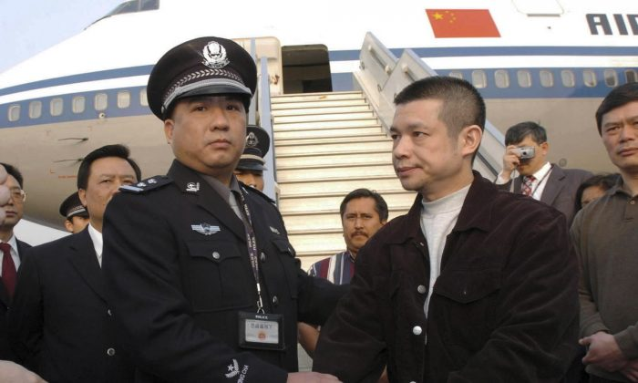 In an April 16, 2004, file photo released by China's Xinhua News Agency, Yu Zhendong, right, is arrested by Chinese police. Chinese officials have gone to great lengths to avoid capture. (AP/Xinhua, Yuan Man, File)