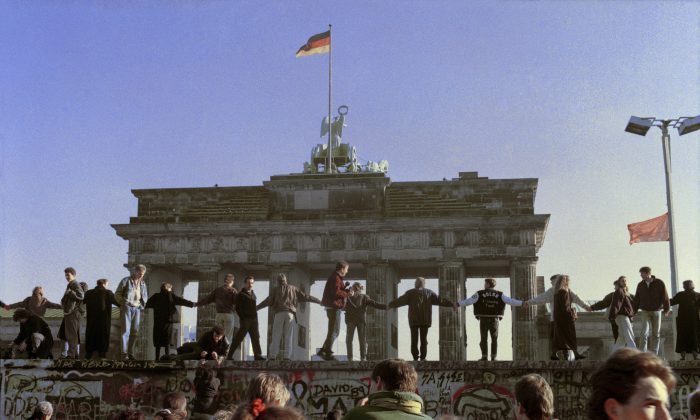 In this Nov. 10, 1989 file photo Berliners sing and dance on top of The Berlin Wall to celebrate the opening of East-West German borders. Thousands of East German citizens moved into the West after East German authorities opened all border crossing points to the West. In the background is the Brandenburg Gate. (AP Photo/Thomas Kienzle)