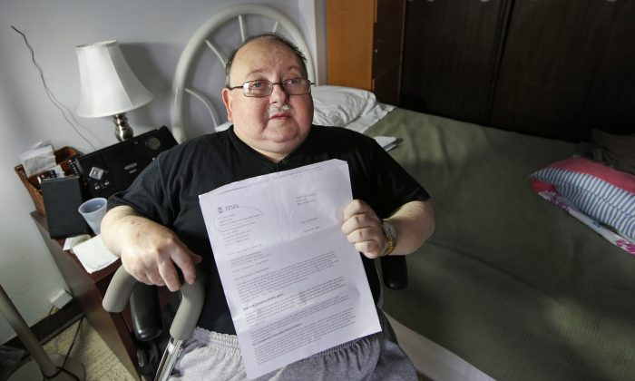 Belle Harbor Manor resident Robert Rosenberg, 61, who suffers from a spinal disability and has other chronic health problems, sits in his room in an assisted living facility in New York on Nov. 6, 2014. Rosenberg holds a letter from the Federal Emergency Management Agency asking him to pay back all the federal disaster aid he received after the storm. He is among a dozen residents of Belle Harbor Manor who have been asked to return aid money. (AP Photo/Kathy Willens)