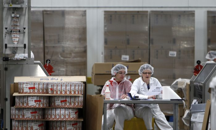 Two employees work in the sleeving plant where labels are put on containers at Chobani Greek Yogurt in South Edmeston, N.Y., on Jan. 13, 2012. New York state's upstate-downstate divide is alive and well, as Tuesday's election results showed. Cuomo has tried to appeal to upstate with talk of yogurt plants, tourism, and economic development initiatives in Buffalo but the numbers show there's still significant differences when it comes to how the two areas view state government. (AP Photo/Mike Groll)