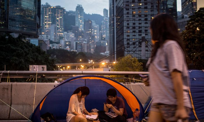 Pro-democracy activists read in a tent on a street outside Hong Kong's Government Complex on Oct. 26, 2014 in Admiralty District, Hong Kong. A student member of Hong Kong Scholarism was refused entry at the customs in the city of Shenzhen, which borders Hong Kong, on Nov. 7, 2014. (Chris McGrath/Getty Images)