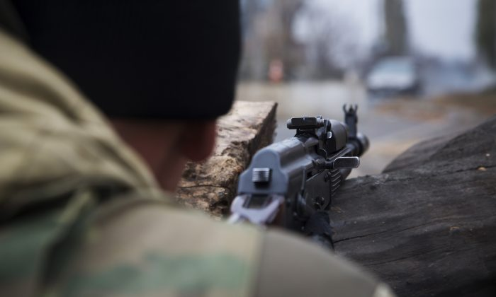 A pro-Russian rebel takes aim at a firing position at a check point not far from Donetsk airport in the city of Donetsk, eastern Ukraine Saturday, Nov. 1, 2014. Fighting intensified in the north of Donetsk between the rebels and government troops ahead of the rebel election on Sunday. (AP Photo/Dmitry Lovetsky)