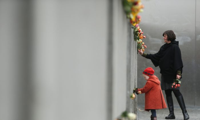 Hulda, 3, places flowers in between slats of the former Berlin Wall at the Berlin Wall Memorial at Bernauer Strasse on the 25th anniversary of the fall of the Wall on November 9, 2014 in Berlin, Germany. (Sean Gallup/Getty Images)