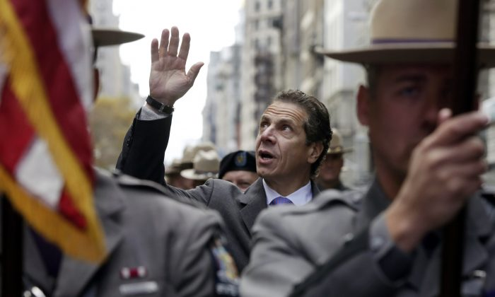 New York Gov. Andrew Cuomo marches in the Veterans Day parade on New York's Fifth Avenue in Manhattan, N.Y., on Monday, Nov. 11, 2013. Cuomo vetoed legislation that would have authorized state and municipal pension credits for peacetime military service. (AP Photo/Richard Drew)