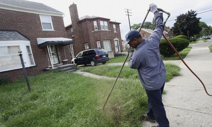 A worker from Homrich turns off water supply to a home in Detroit on Aug. 27, 2014. The Detroit Water and Sewer Department has disconnected water to thousands of Detroit residents who are delinquent with their bills. (Joshua Lott/Getty Images)
