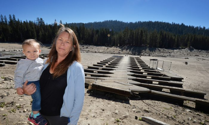 Marina owner Mitzi Richards carries her granddaughter as they walk on their boat dock at the dried up lake bed of Huntington Lake, as a severe drought continues to affect California, on Sept. 23, 2014. (Mark Ralston/AFP/Getty Images)