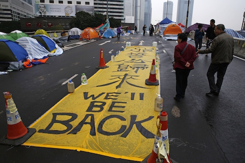 "A yellow banner reading ""We'll be back"" is displayed by protesters at the occupied area outside government headquarters in Hong Kong Wednesday, Dec. 10, 2014. (AP Photo/Kin Cheung)"
