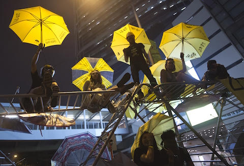 Protesters pose for photographs on a barricade at the occupied area outside government headquarters in Hong Kong Wednesday, Dec. 10, 2014. (AP Photo/Kin Cheung)