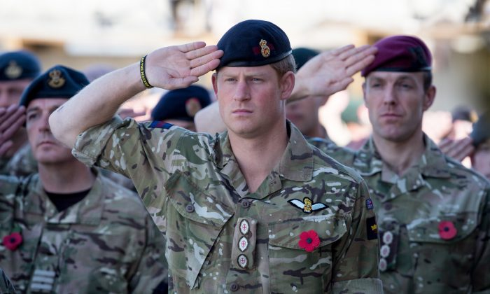 Prince Harry salutes as the Last Post is played as he joins British troops and service personal remaining in Afghanistan and also International Security Assistance Force (ISAF) personnel and civilians as they gather for a Remembrance Sunday service at Kandahar Airfield November 9, 2014 in Kandahar, Afghanistan. (Matt Cardy/Getty Images)